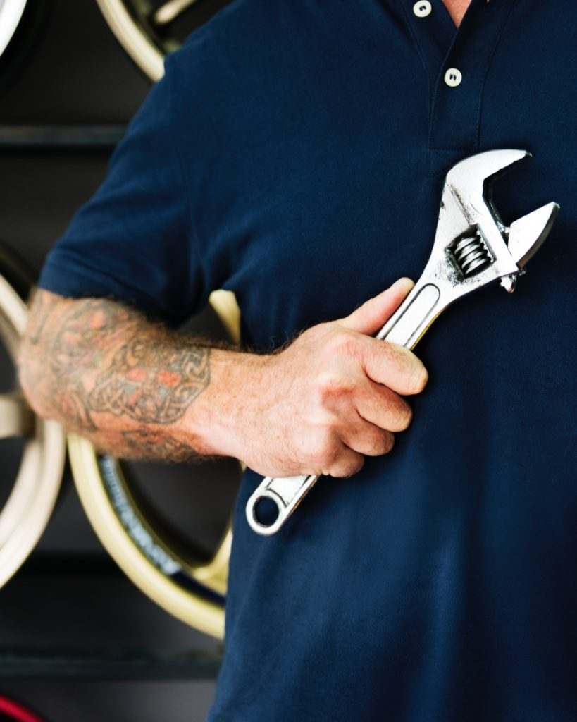 Male mechanic holding a wrench