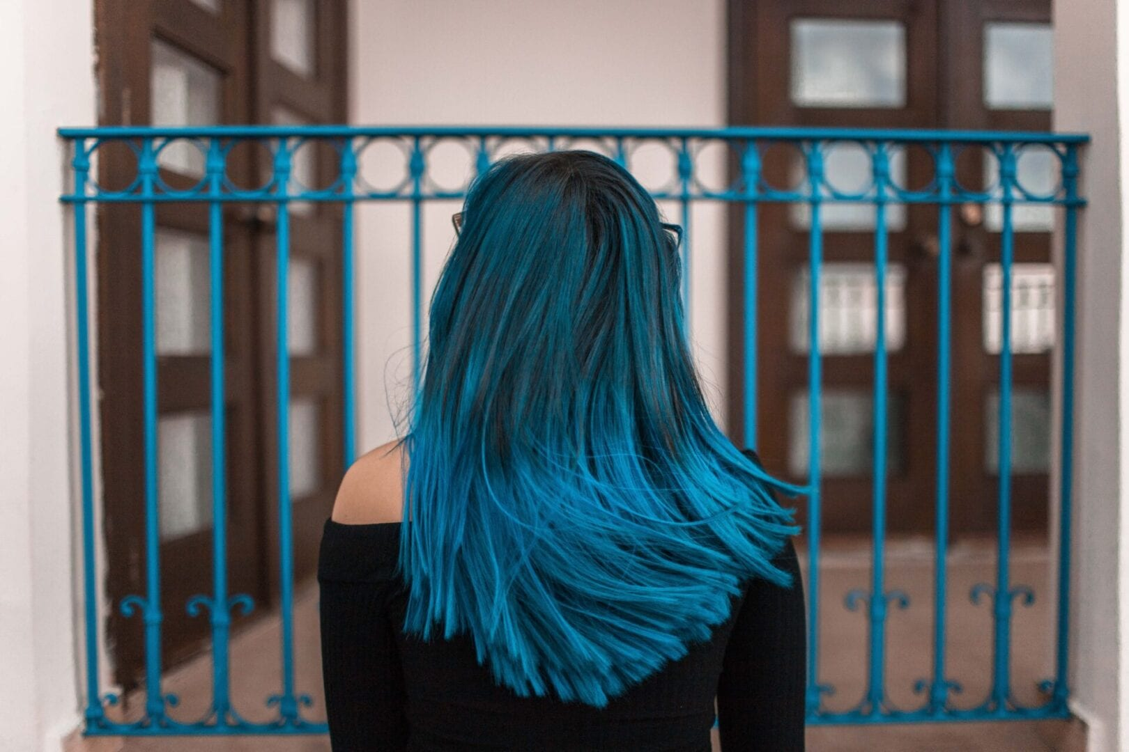 blue-haired-woman-facing-metal-fence-1510542