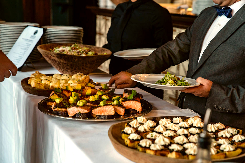 Male server in suit plating salmon and salad for guests during private event