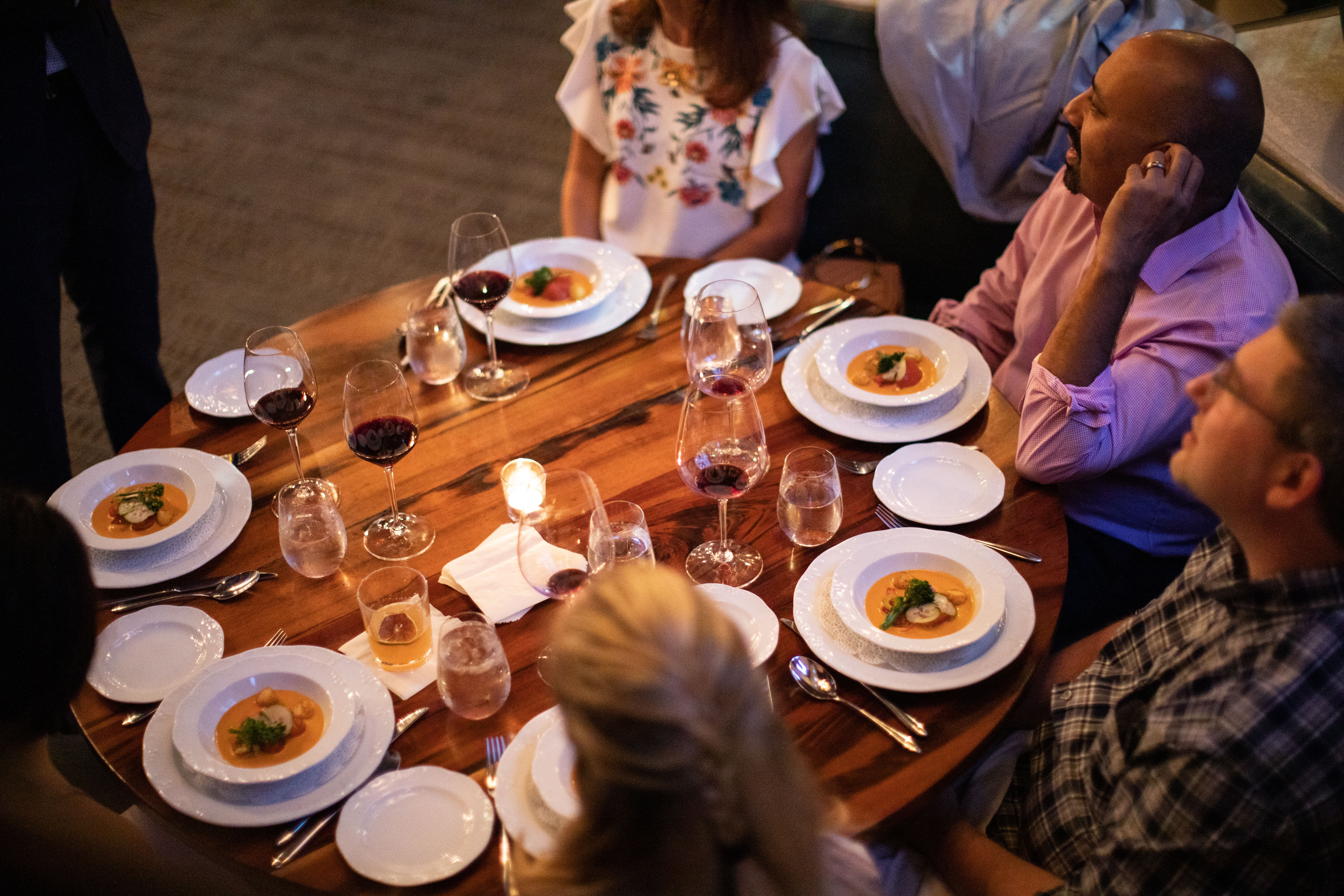 Group of diners at round table during private event with soups and glasses of wine