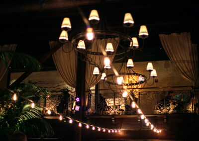 Chandeliers and string lights below balcony with tables