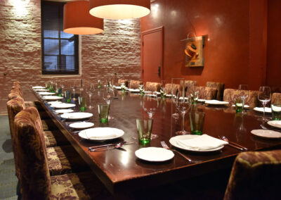 Large wooden table set for 20 people in conference room style