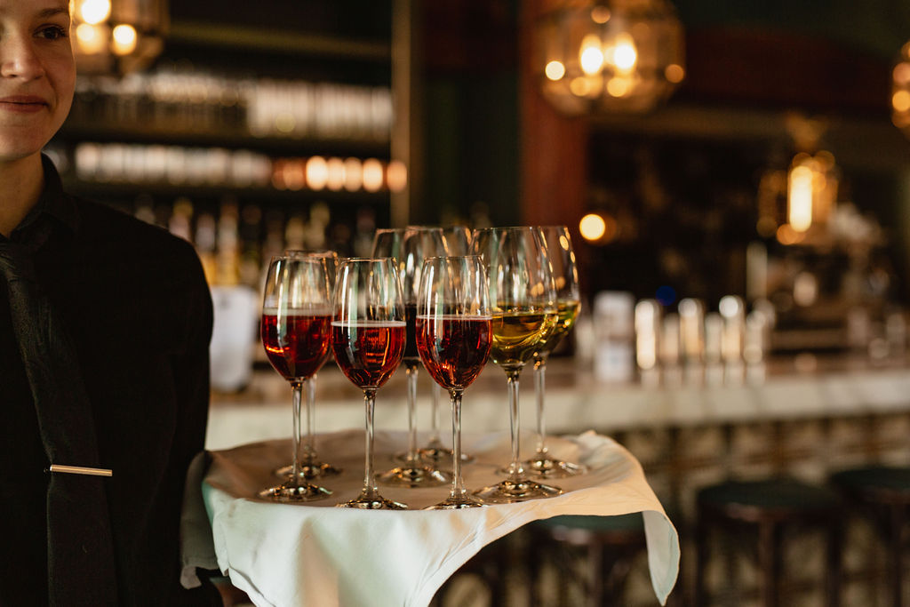 Female server in black uniform with tray of glasses of sparkling rosé and white wine