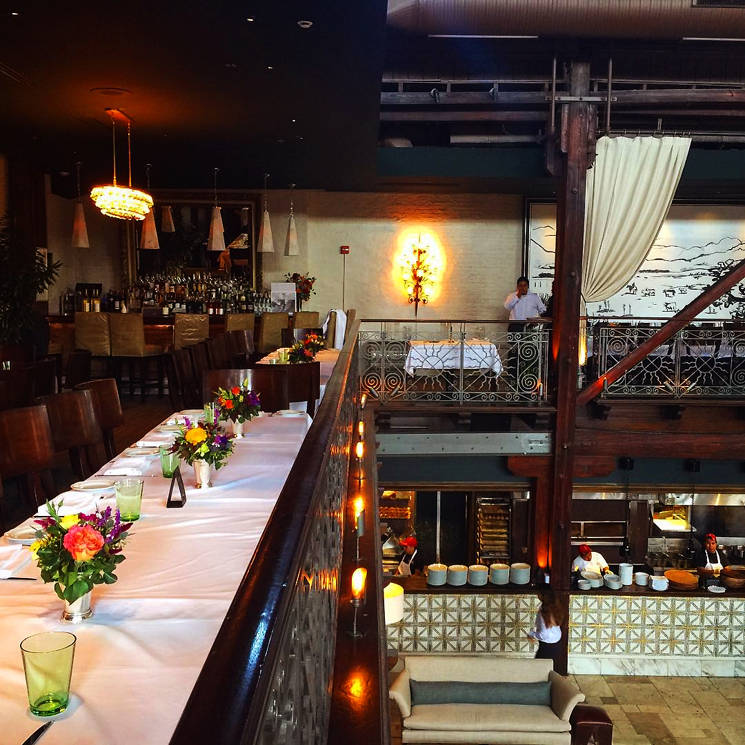 Tables along balcony or mezzanine with white table clothes and flowers for wedding reception