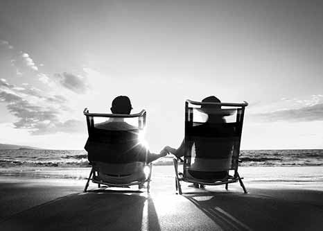 black and white photo of two people on the beach