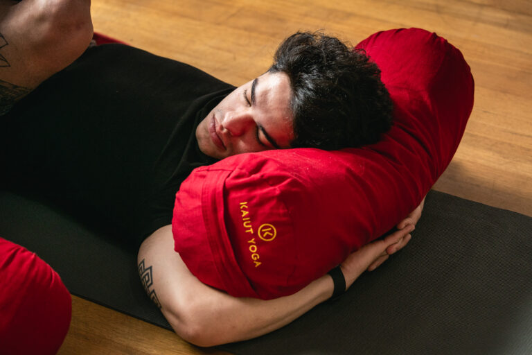 Close up of student lying down with head on bolster, hands interlocked underneath, neck turned to left