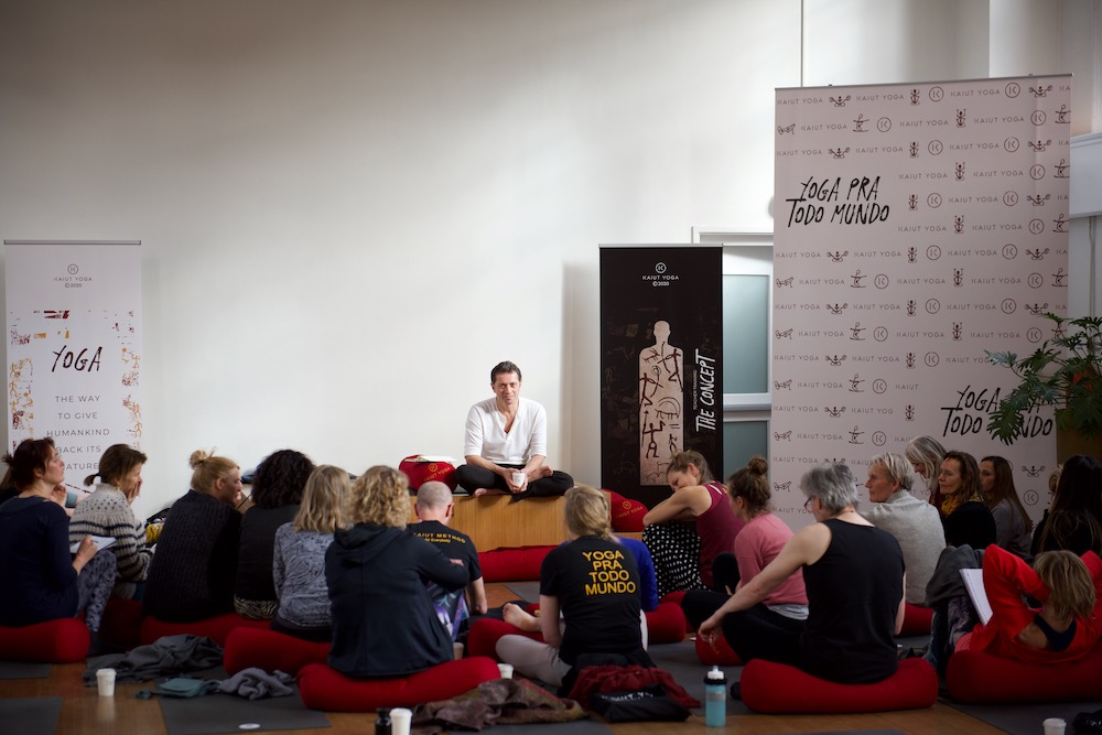 Francisco Kaiut sitting on a platform talking to a group of students seated in front of him