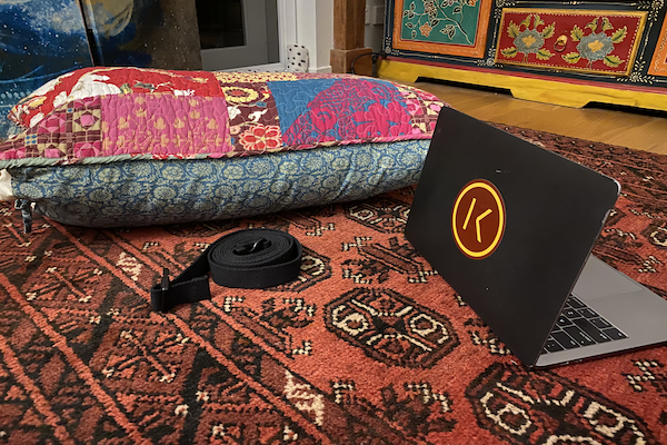 Home practice equipment of colorful pillow, black strap, and computer with Kaiut Yoga sticker on a patterned rug