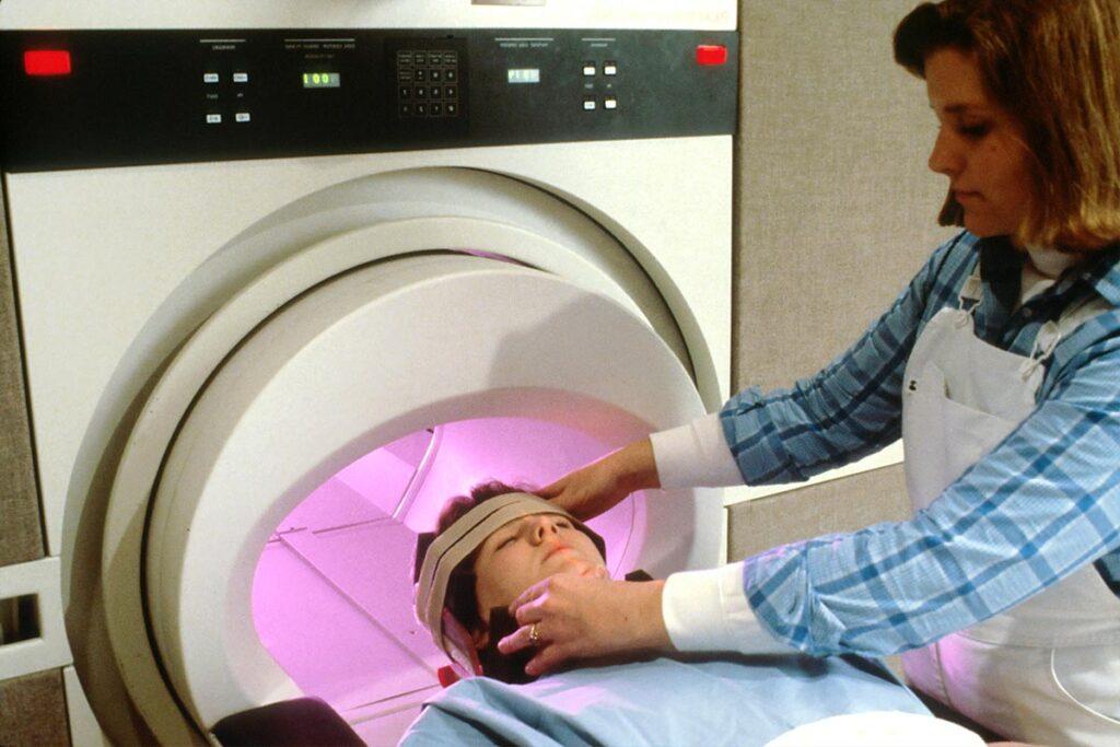 MRI technologist adjusting patient