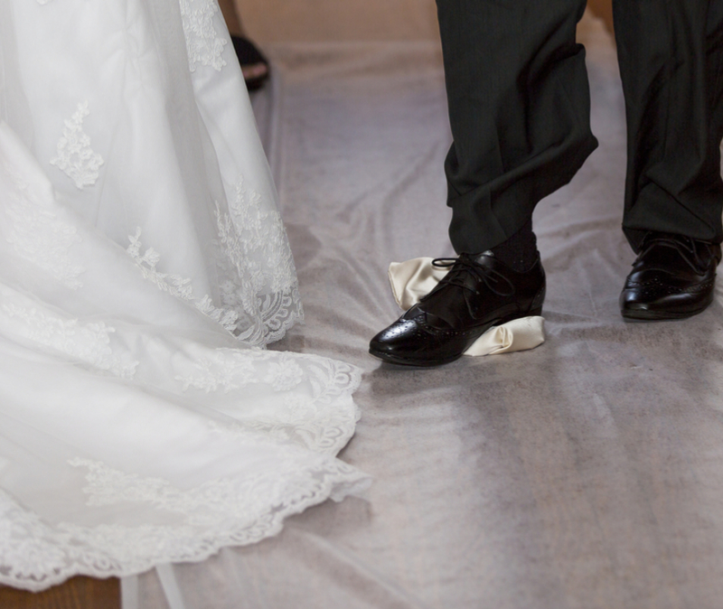 Groom breaks glass at Jewish wedding. Bride stands alongside. View is from the knee down