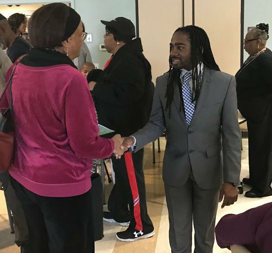 Trayon White shakes the hand of a constituent