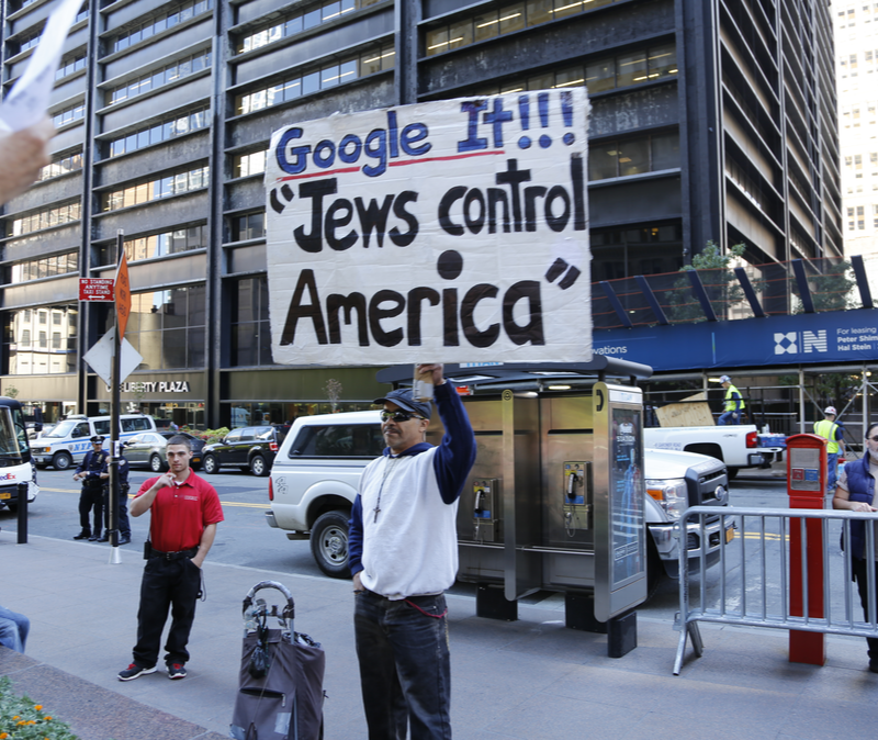 NEW YORK CITY - SEPTEMBER 17 2014: Occupy Wall Street marked the third anniversary of its founding as several dozen activists gathered in Zuccotti Park.David Smith with sign denouncing Jewish hegemony