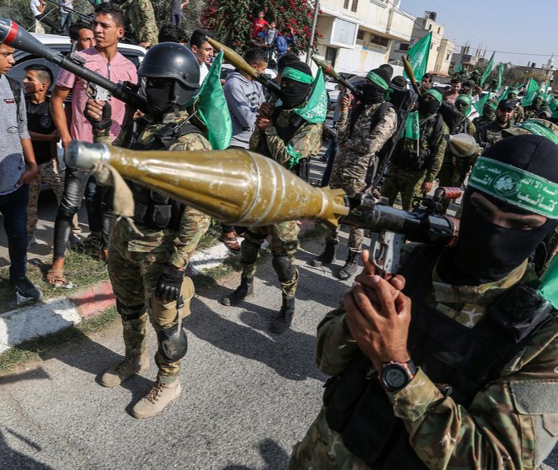 Hamas terrorists display rocket during rally