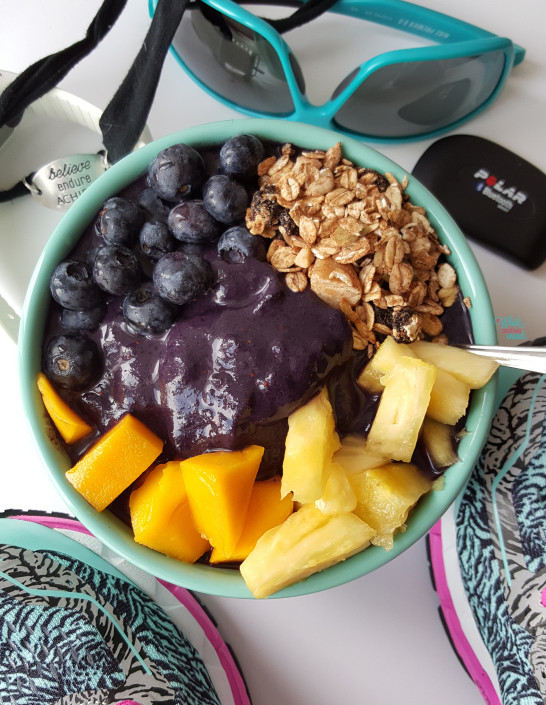 Acai Protein Smoothie Bowl made with vanilla protein, all acai juice, bananas, and blueberries. Topped with fresh blueberries, mango, pineapple, and muesli. (vegan and gluten free)