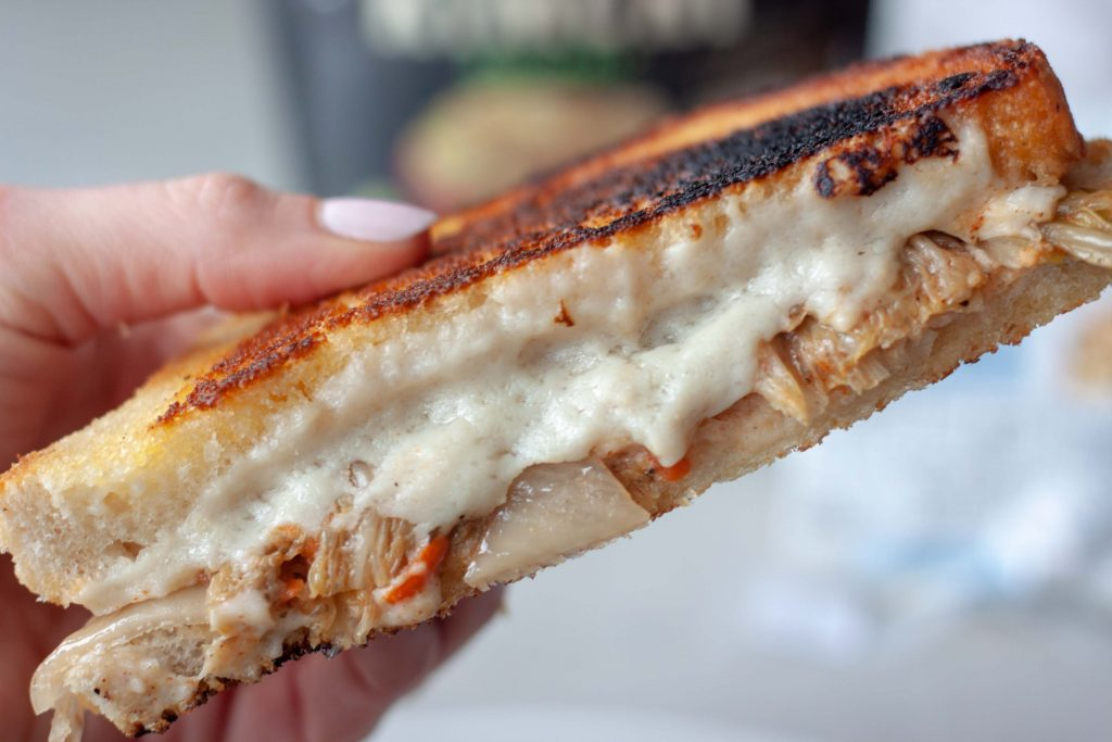 Holding a sourdough grilled cheese sandwich with kimchi