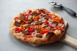 sausage pizza on wood board