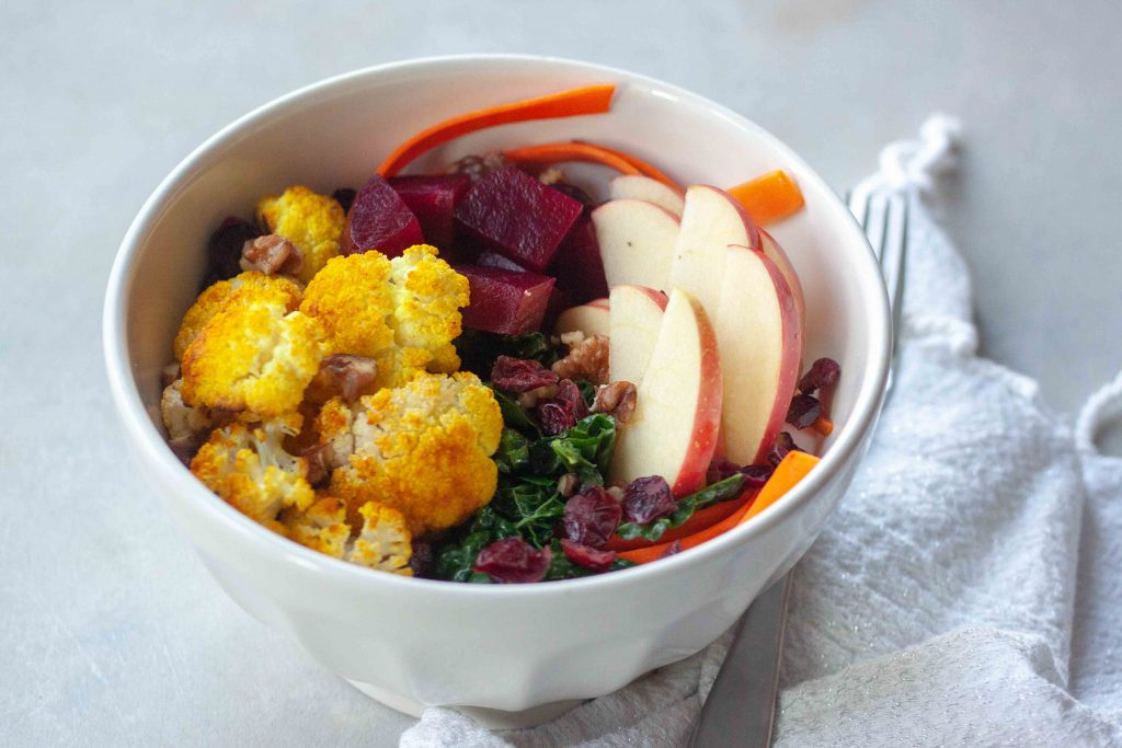Buddha Bowl packed with anti- inflammatory whole foods, kale, beets, turmeric cauliflower, cranberries, apples, carrots, and walnuts.