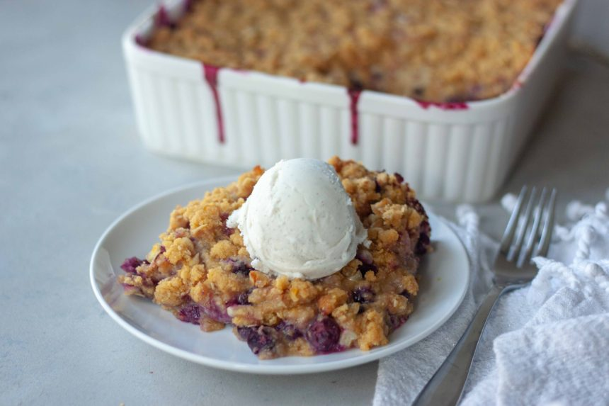 Piece of Sweet Corn Blueberry Crisp topped with ice cream