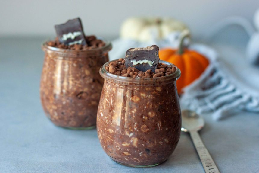 Two Overnight Oat Graveyard Cups with mini pumpkins and spoon