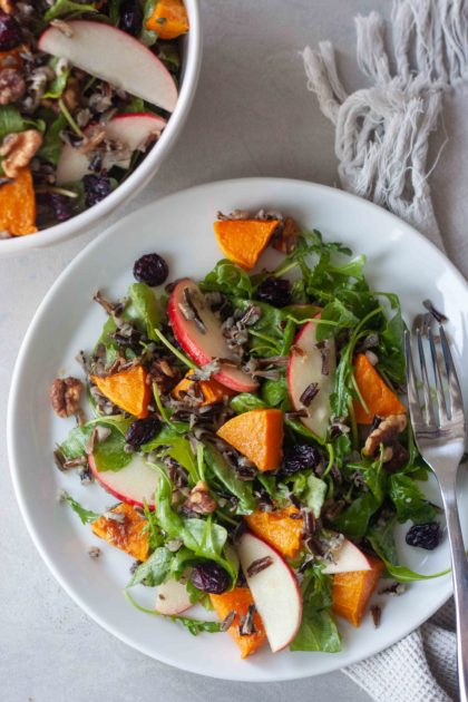 Plate of Wild Rice Roasted Butternut Squash Salad with fork, bowl in background.