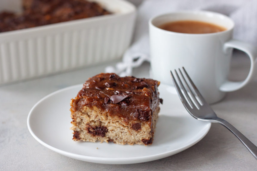 Slice of Date Caramel Chocolate Chip Baked Oatmeal on plate with fork, coffee in coffee cup, pan of oatmeal bake