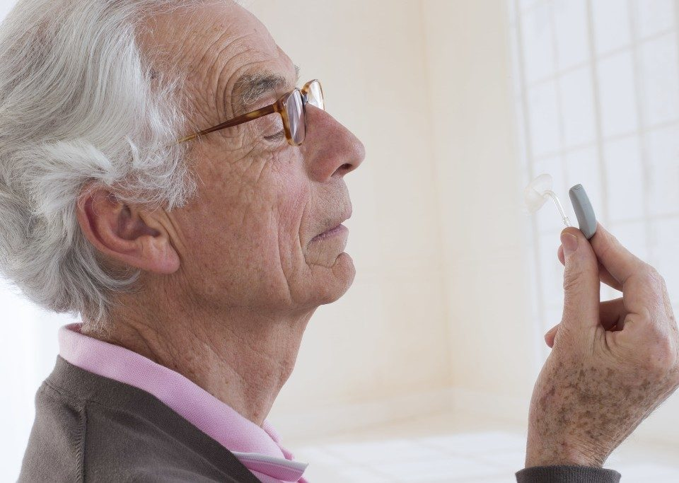 senior citizen looking at hearing aid