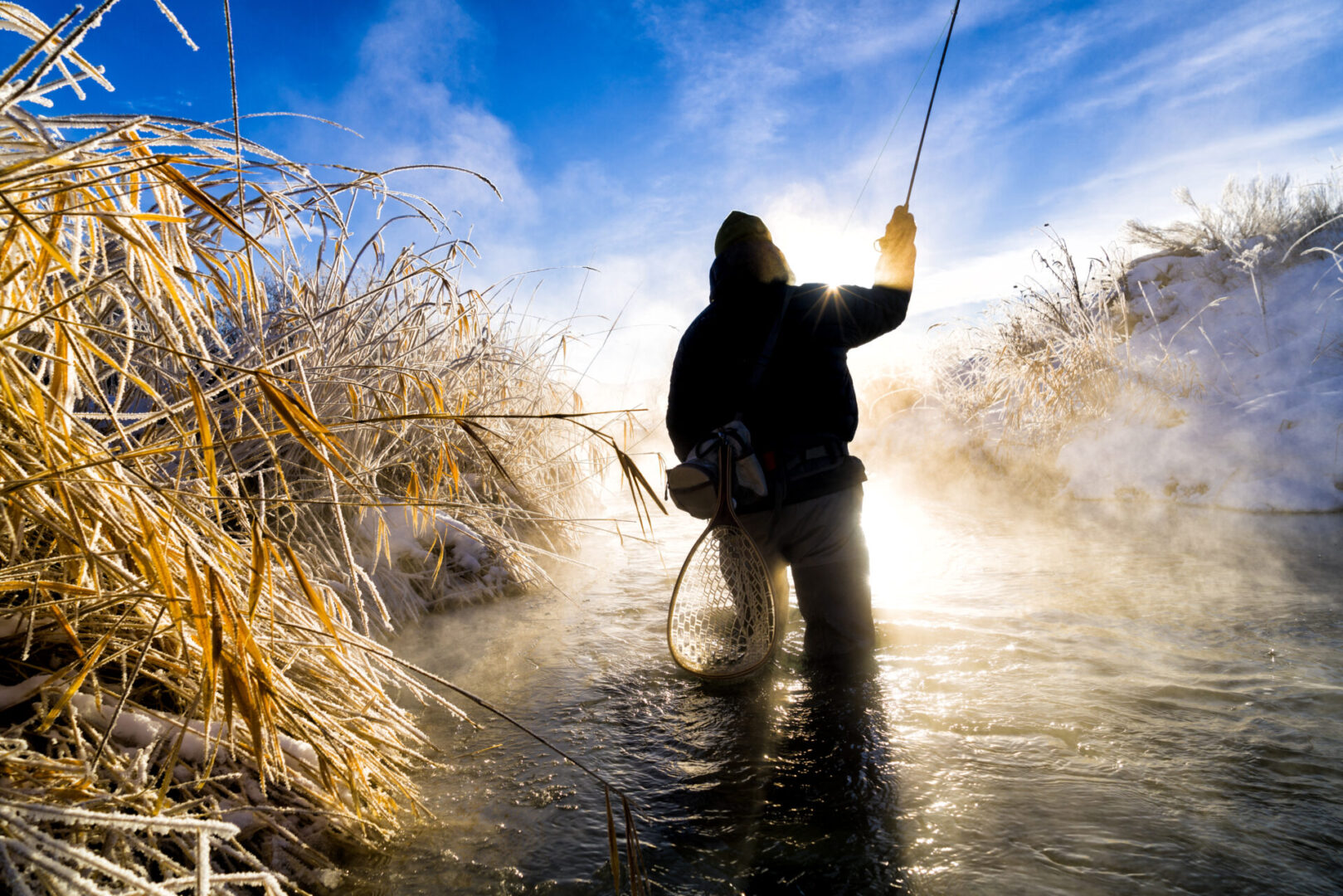 Fly Fishing in Extreme Cold Winter Conditions - Scenic winter landscape with fly fisherman recreating on cold trout mountain stream.  Colorado, USA.