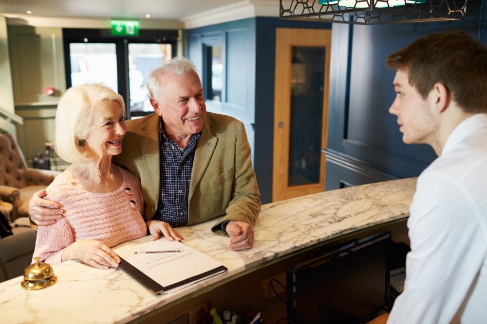 elder-couple-checking-into-hotel