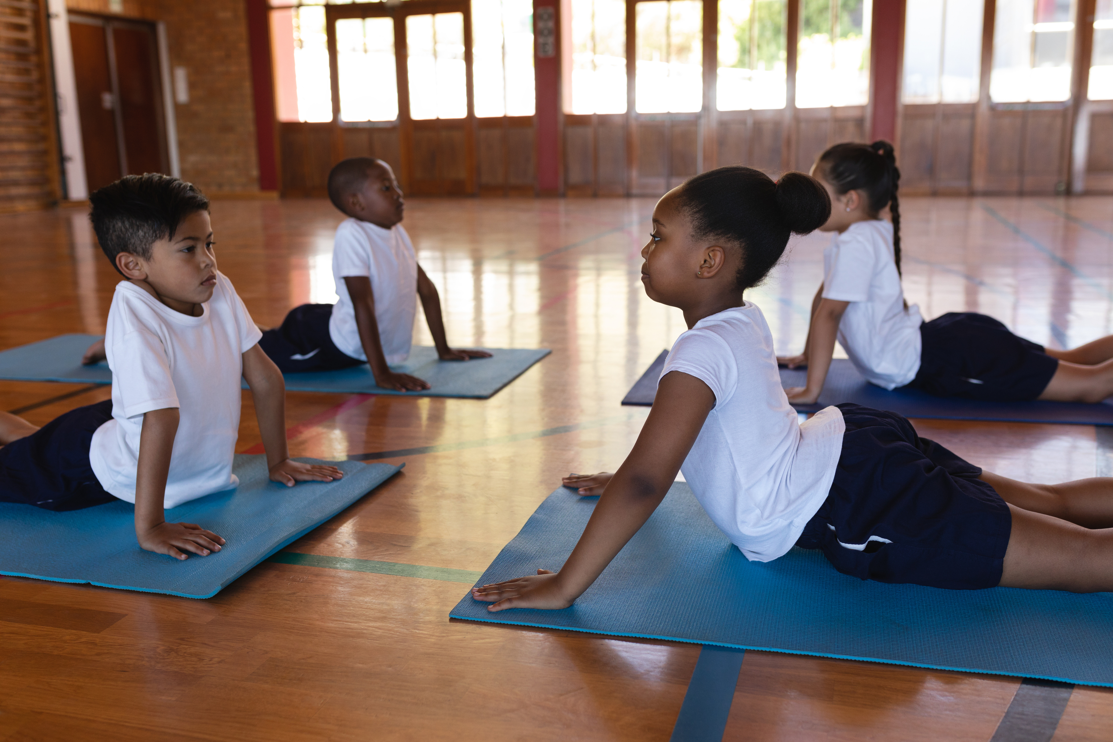 Side view of concentrate schoolkids doing yoga position on a yoga mat in school