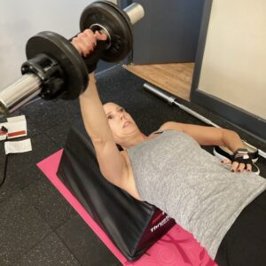 Tina doing one arm dumbbell bench presses in my Boonton personal training studio