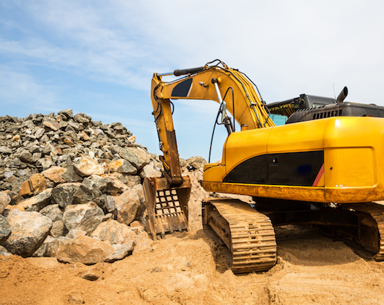 yellow excavator, pile of rocks