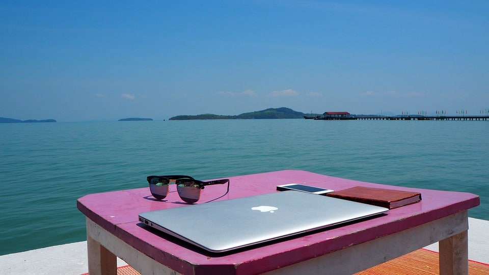 An image of a laptop, cell phone, and sunglasses sitting atop a table, overlooking a body of water.