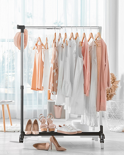 Collection of clothes hanging on rack in dressing room