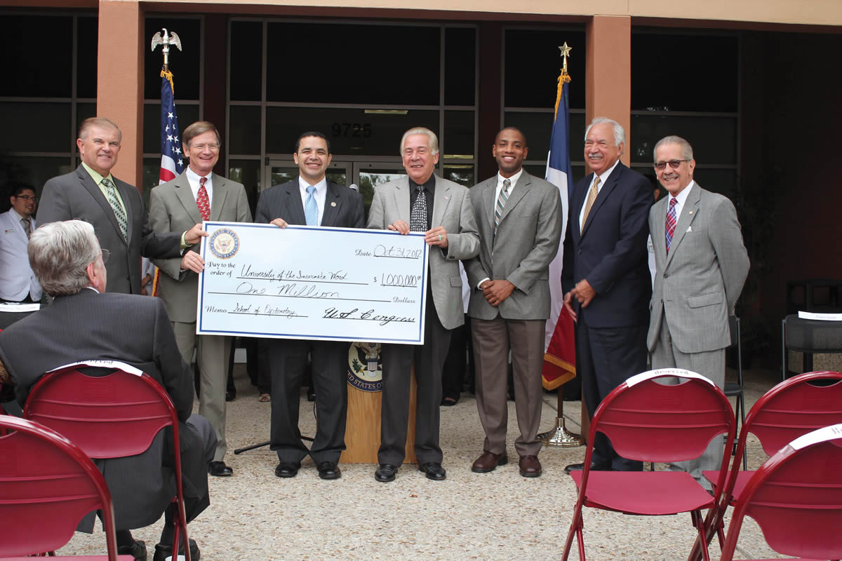 RSO Dean Dr. Andrew Buzzelli; U.S. Congressman Lamar Smith (R-TX-21); U.S. Congressman Henry Cuellar (D-TX-28); President Dr. Louis Agnese; UIW Grant Writer Armando Saliba; EDA Regional Director Pedro Garza; and UIW Director of Foundation, Corporate & Government Relations Robert Sosa display a check for $1 million awarded to UIW by the Economic Development Administration (EDA) during a press conference held on Oct. 31.
