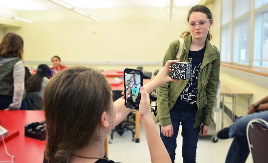 Two attendees explore augmented reality on mobile devices.
