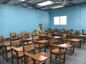 Speer takes a seat inside a classroom in Guatemala.