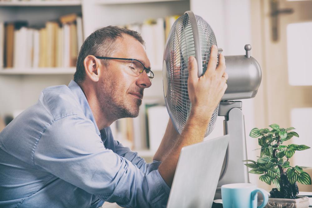 man sitting in front of a fan