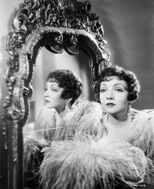 Portrait of actress Claudette Colbert standing next to an ornate