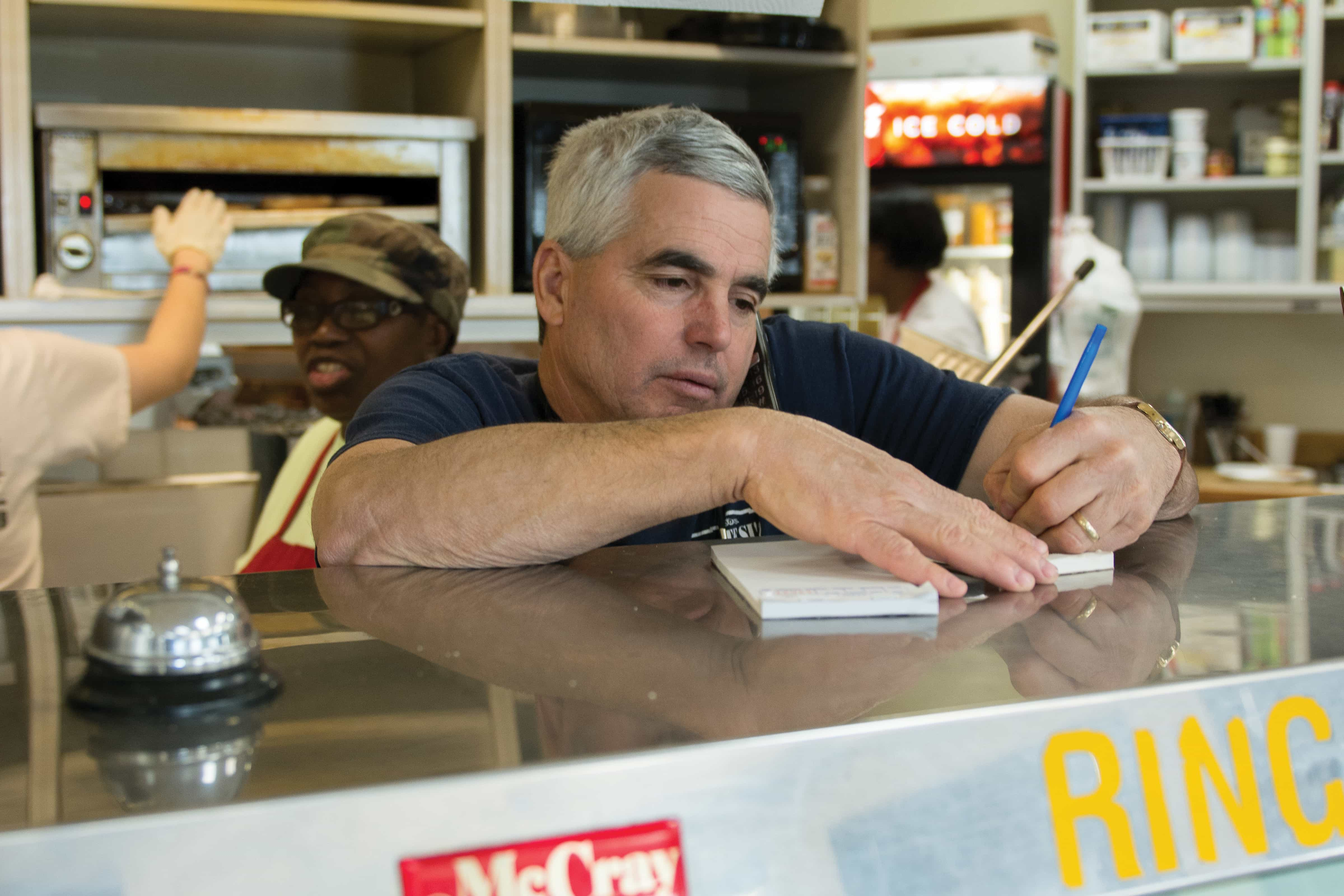 Kenny Fratesi takes customer's orders over the phone.