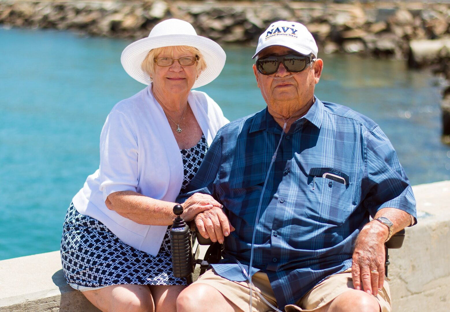 older couple sitting by the water.  Man has an oxygen cannula in his nose and a NAVY cap and is sitting in a wheel chair.