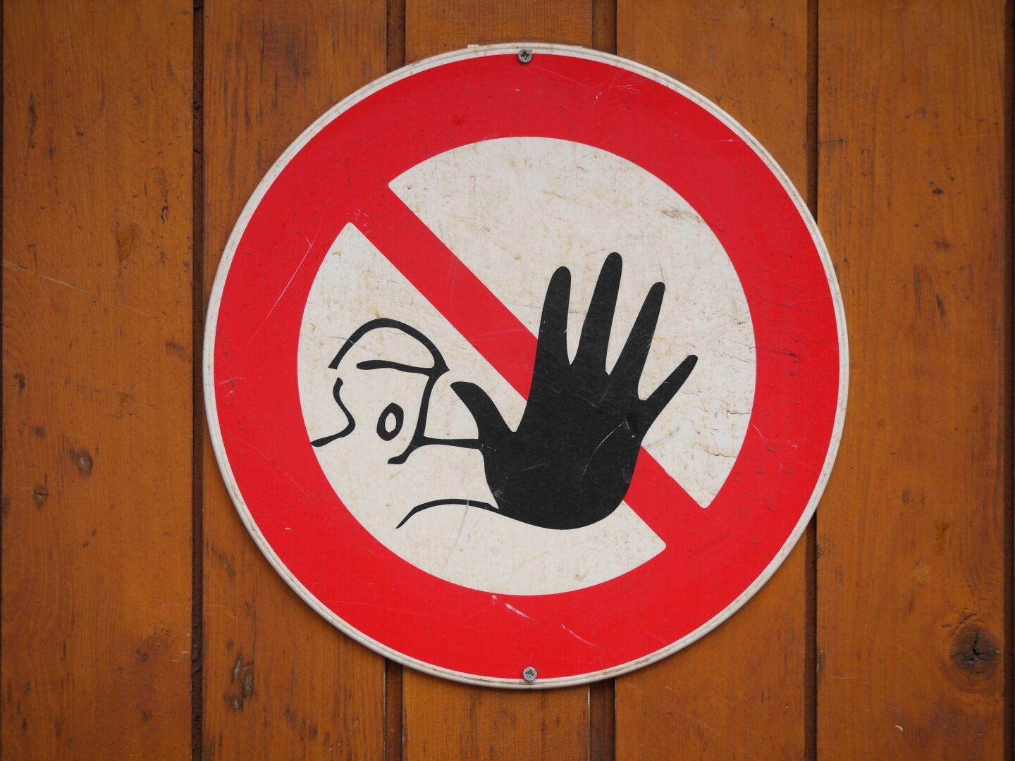 Hand though a don't enter sign