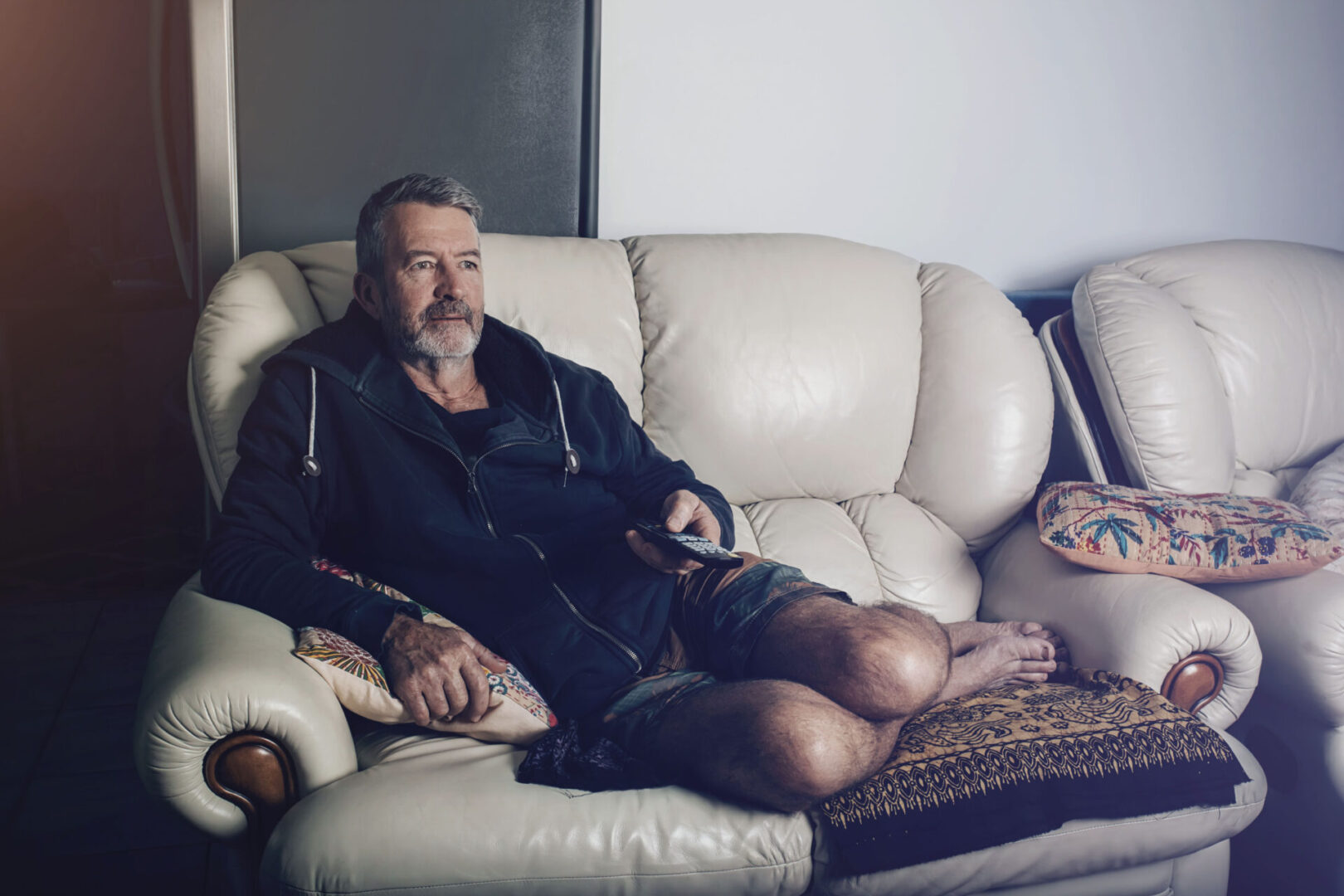 Man sitting on couch in a bathrobe watching TV