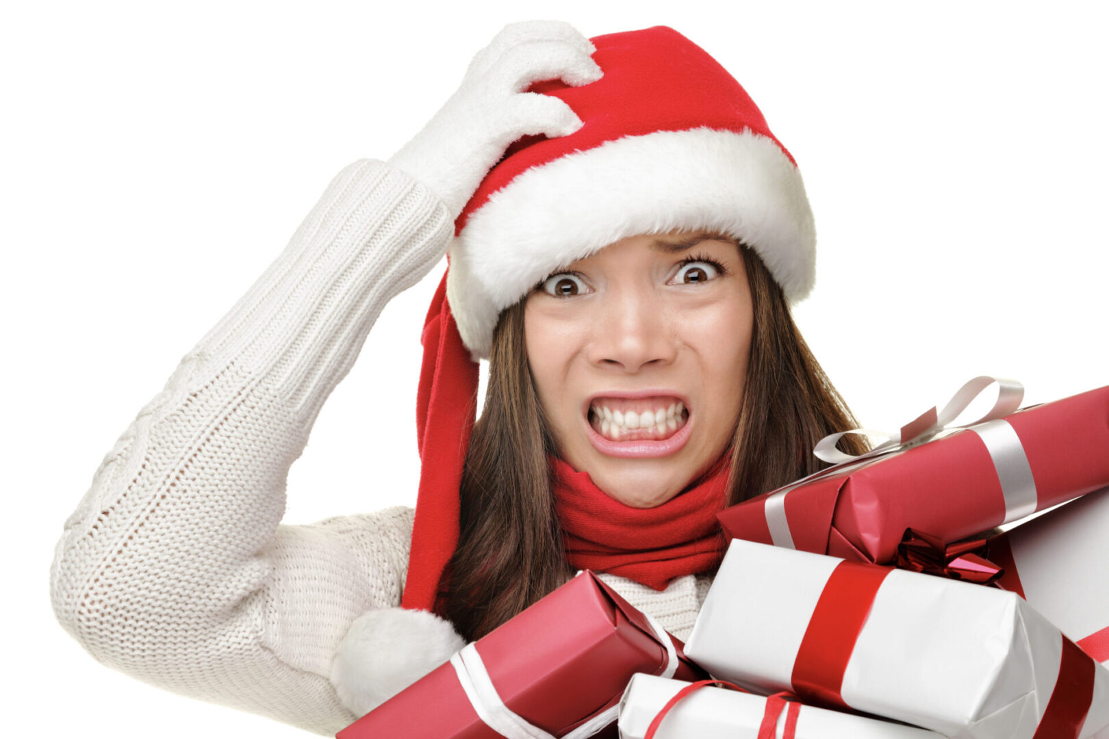 Woman grabbing santa hat grimacing with lots of presents in her hand