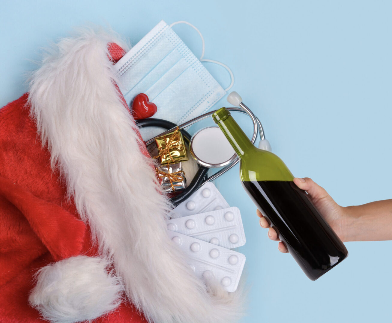 Christmas Stocking with stethescope, pills and a heart. Hand with wine bottle