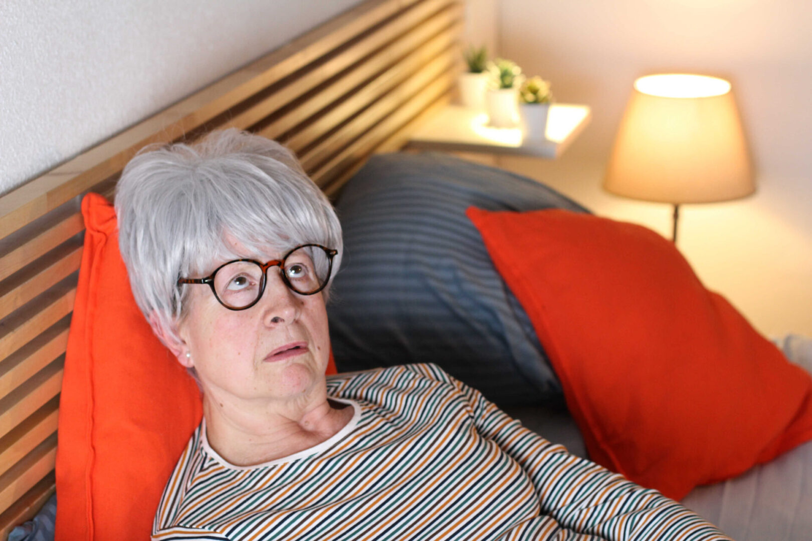 Woman with Gray hair and glasses lying in bed and looking up at the sky as if in despair.