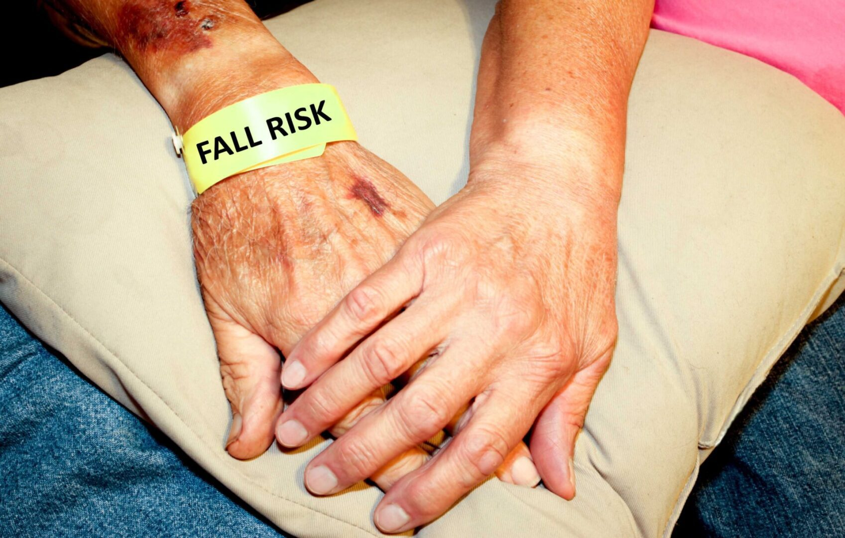 Older hand with FALL RISK yellow band being held by a youger hand on a tan pillow