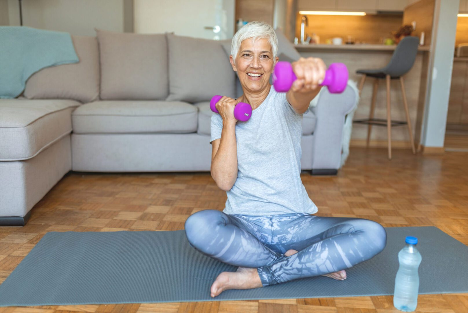 Woman with short grey hair working out with pink dumbells on a mat in her living room
