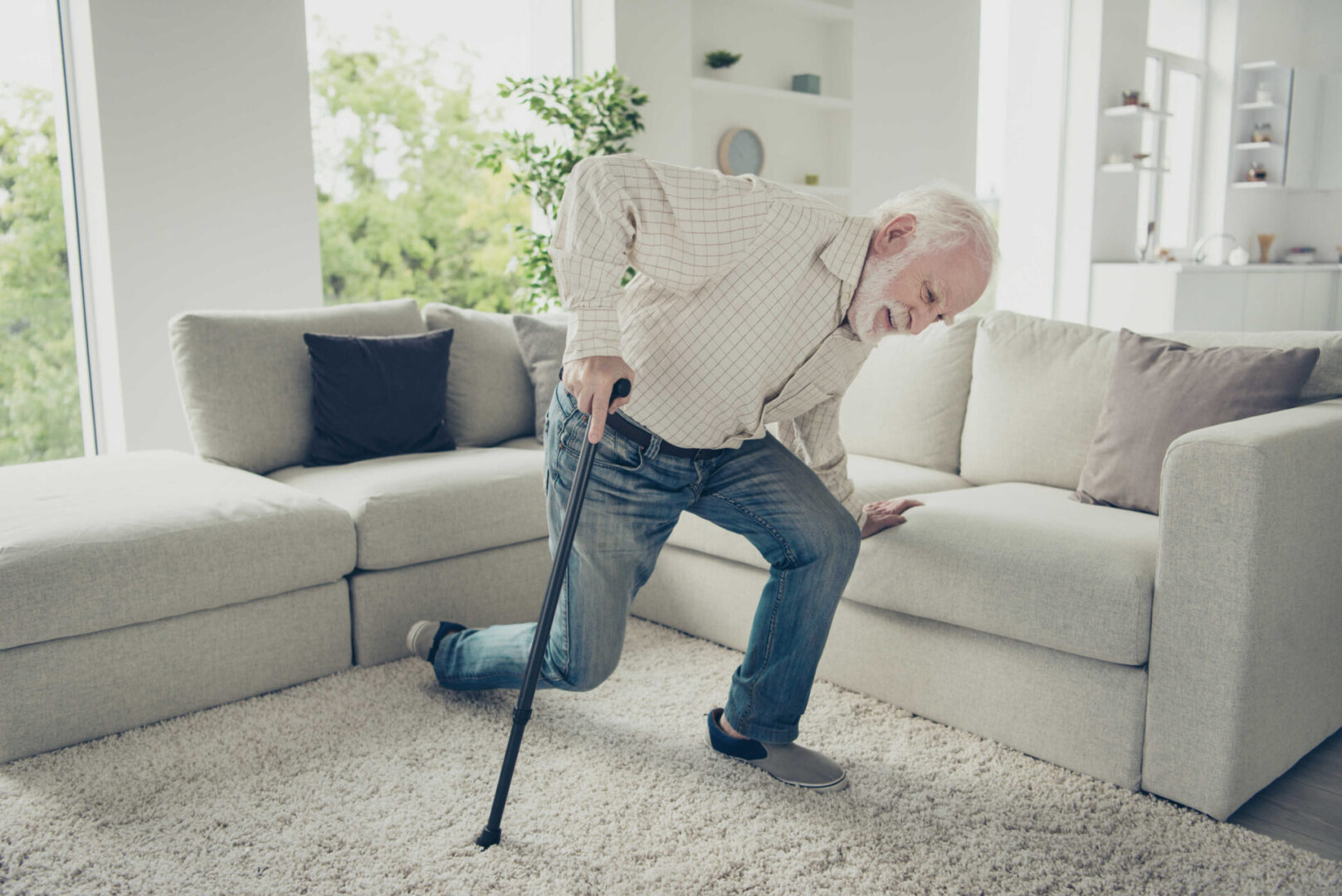 Older man stumbling getting off of white couch