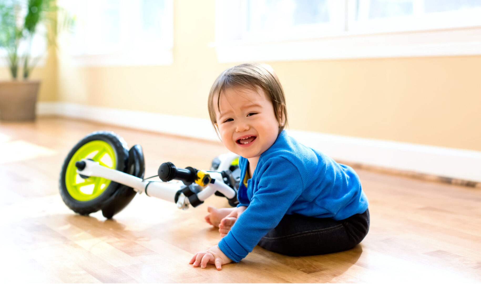 Baby on the floor with bike