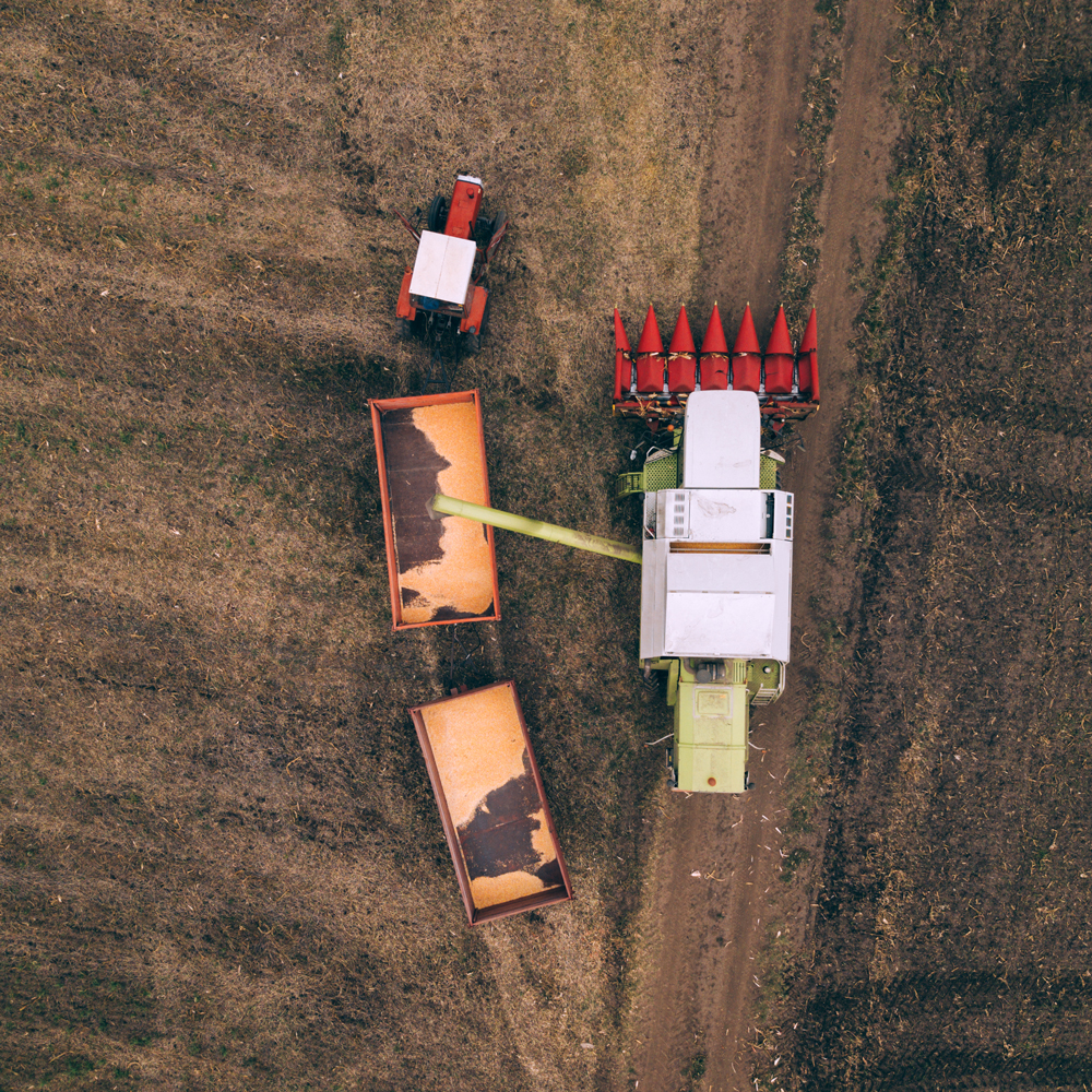 aerial-view-of-combine-pouring-harvested-corn-grai-compressed